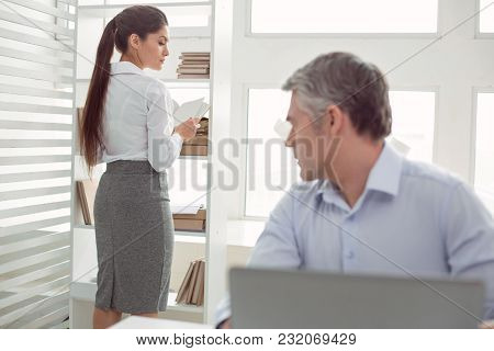 In The Office. Nice Pleasant Handsome Man Sitting At The Table And Looking At His Colleague While Fe
