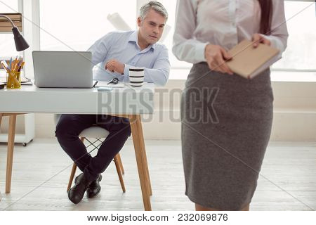 At The Office. Smart Nice Adult Man Sitting At The Table And Pretending To Work While Looking At His