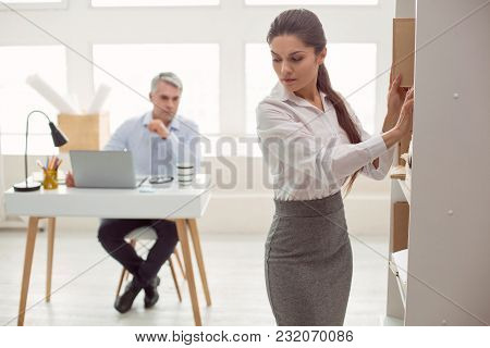 Unpleasant Feeling. Nice Attractive Pleasant Woman Standing Near The Shelf And Turning Her Head Whil