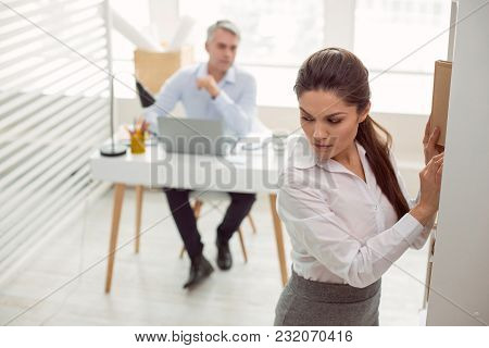 Office Worker. Pleasant Attractive Young Woman Standing In The Office And Working While Being Looked