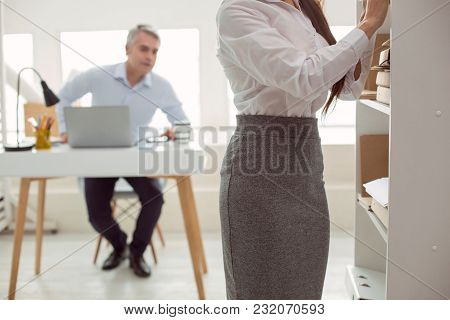 Office Worker. Beautiful Pretty Young Woman Standing Near The Shelf And Working While Being Looked A