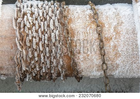 The Frozen Rusty Chain Is Wound On A Log, To Raise A Bucket Of Water From An Old Well, A Frosty Day.