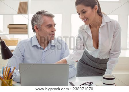 Pleasant Communication. Joyful Positive Nice Woman Standing Near Her Colleague And Smiling To Him Wh