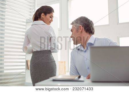 Inappropriate Behaviour. Serious Confident Nice Man Sitting At The Office Table And Showing His Inte