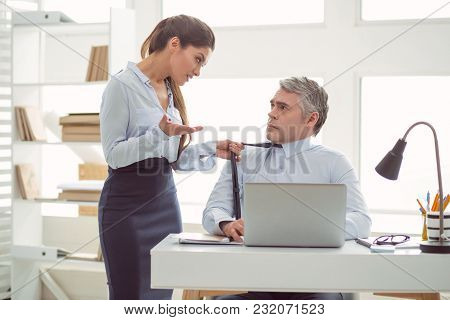 Relations Between Colleagues. Nice Pleasant Young Woman Holding A Mans Tie And Talking To Him While