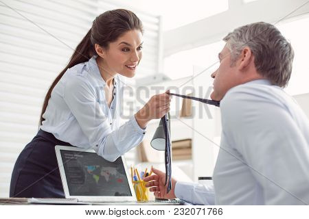 In The Office. Attractive Nice Young Woman Standing Opposite Her Colleague And Talking To His While