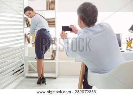 Take Away The Camera. Cheerless Nice Young Woman Standing Near The Shelf And Looking At The Man Whil