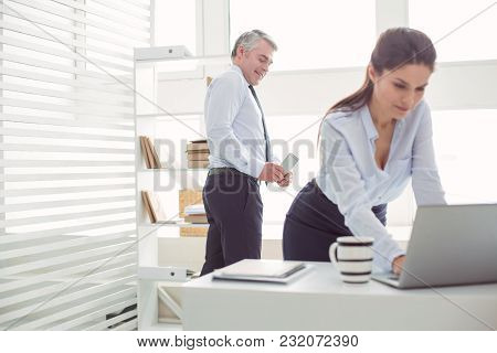 Gender Discrimination. Unpleasant Cheerful Adult Man Standing Behind His Colleague And Taking A Phot