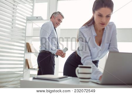 Social Problem. Unpleasant Happy Adult Man Standing In The Office And Looking At His Secretary While