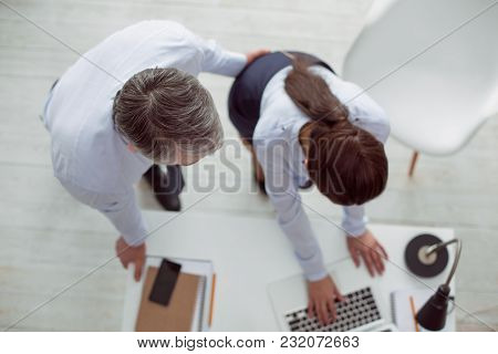 Unpleasant Situation. Top View Of Two Colleagues Standing Around The Table And Working While The Man