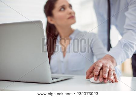 Sexual Abuse. Nice Pleasant Young Woman Sitting At The Table And Working While Feeling A Male Hand O