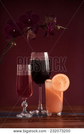 Alcohol Drinks (red Wine, Sparkling Wine, Grapefruit Cocktail) On Dark Solid Red Background