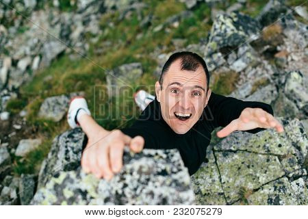 Young Man Makes Hard Climbing A Steep Rock Without Rope.