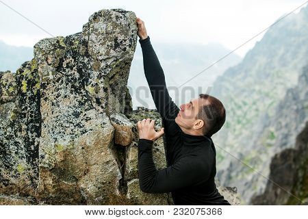 Young Man Climbs The Rock Against Mountain Background.