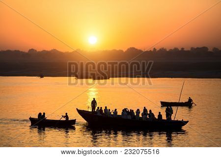 Dawn on the Ganges river, with the silhouettes of boats with pilgrims. Varanasi, India.
