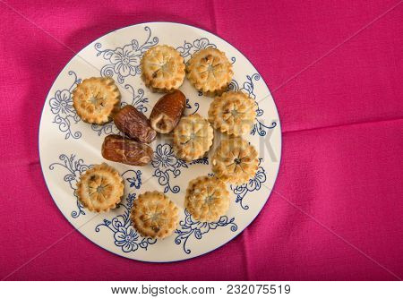 Arabic traditional cookies - Maamoul, arrange on the plate with whole dates. Traditional middle eastern dessert recipe.