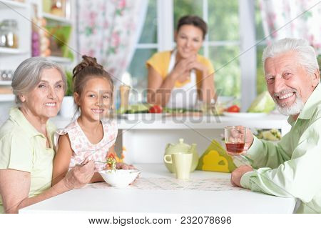 Happy Senior Couple With Granddaughter Dinner Together