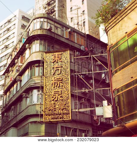 Hong Kong - August 2017: Bottom view of a street with signboard in golden light. Kowloon