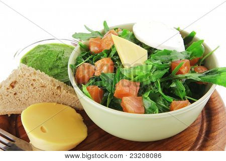 green salad with smoked salmon and bread in green bowl