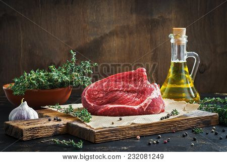 Raw Beef Fillet On A Cutting Board, Thyme, Olive Oil. Ingredients For The Preparation Of Stacks