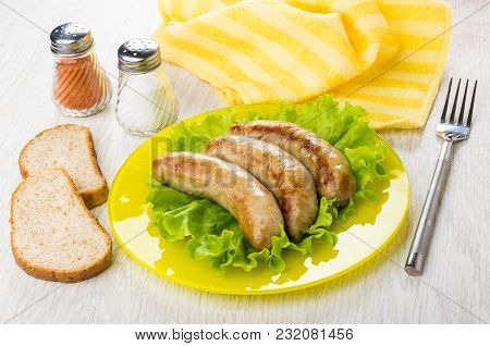 Fried Chicken Sausages On Leaves Of Lettuce In Plate, Napkin, Pieces Of Bread, Pepper, Salt And Fork