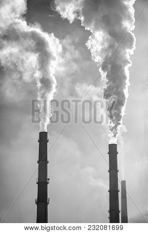Factory Chimneys Smoke In The Background Of Cloudy Sky. Black And White Photo
