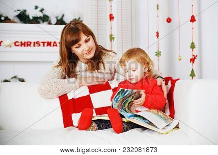 A Little Girl With Her Mother Reads A Book In The Interior With New Year's Decorations.