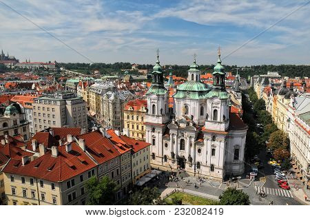 Aerial View Of The St. Nicholas Church And Red Roofs In The Old Town Square In Prague, Czech Republi