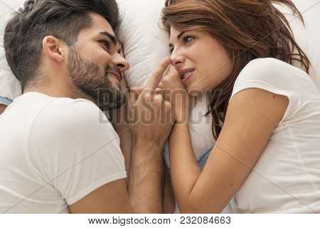 Top View Of A Couple In Love Lying In Bed Next To Each Other, Resting And Cuddling