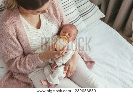 Home portrait of a newborn baby with mother on the bed. Young mom feeding her child from bottle.