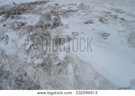 Spring Background Is A Dirty Loose Snow Melting Outdoors.