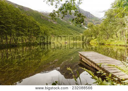 Old Wooden Pier On Lake Pond In Summer, Peaceful Norwegian Landscape, Mountains In The Background