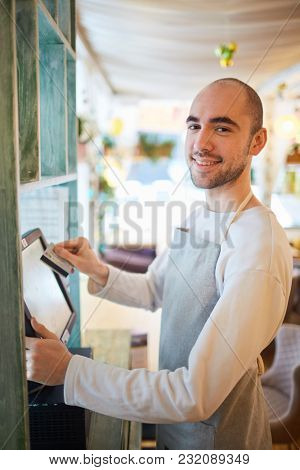 Handsome waiter swiping credit card through the computer terminal in cafe