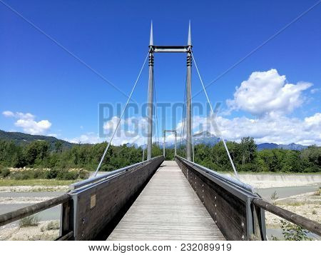 Bike Bridge Over A Mountain River. A Narrow Bridge With Wooden Planks As A Roadway For Pedestrians A