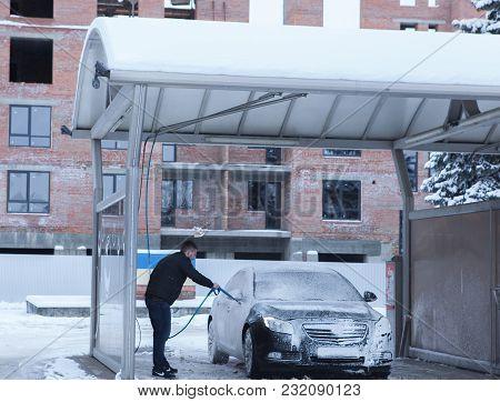 Man Worker Washing Car's Alloy Wheels On A Car Wash. Concept Of Car Wash