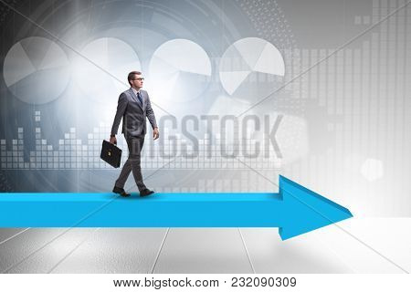 Businessman walking on arrow in business concept