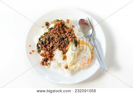 Rice Topped With Stir-fried Pork And Basil Serve With Fried Egg On White Plate & Spoon, Fork Set On
