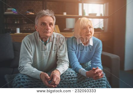 Two Old People Are Sitting Together. They Put Their Hands Over The Knees And Looking Straight Forwar