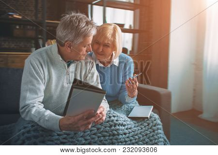 Two Senior People Are Sitting On The Couch And Chosing Cd Disk For Watching Movie. Also They Are Loo