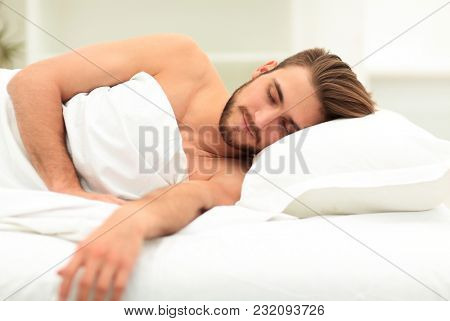 smiling man sleeping on a comfortable bed.