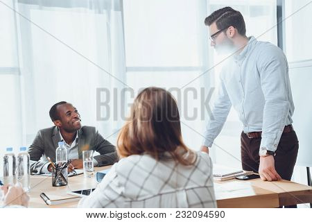 Smiling Multiethnic Businesspeople At Meeting In Office