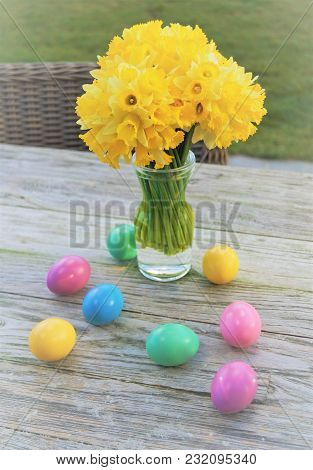 Daffodils And Easter Eggs. Yellow Daffodils And Pastel Colored Easter Eggs In A Glass Vase On A Rust