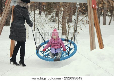 Cute Little Girl Swinging On A Swing On The Playground In Winter, Winter Family Entertainment Concep