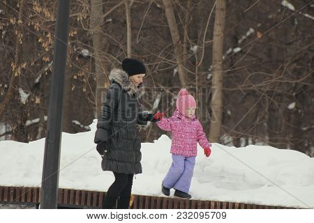 Cute Little Girl Walking With Her Mother On Winter Street, Daughter Breaking Out And Going Independe