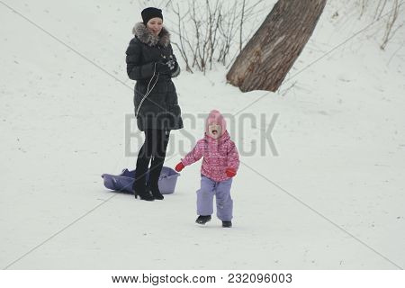 Mom Seating His Disobedient Daughter In Sled On Winter Street, Winter Family Entertainment Concept
