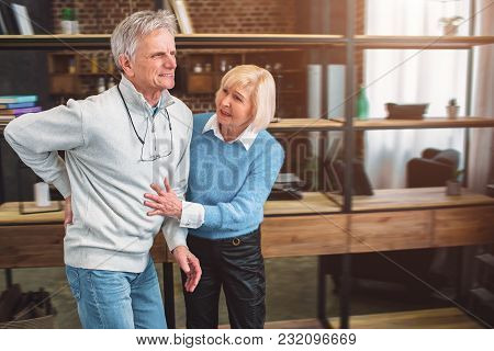 A Picture Of Old Man Keeping His Hand On The Back. He Has A Pain In The Spine. The Woman Wants To He