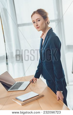 Businesswoman In Formal Suit Standing Against Table With Laptop At Office Space