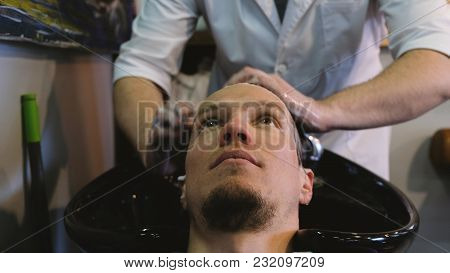 Hairdresser Man Washing Hair With Shampoo In The Barbershop
