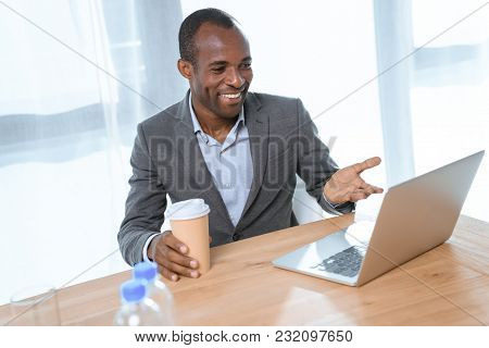 Smiling African Man With Cup Of Coffe Smiling While Looking On Laptop On Table