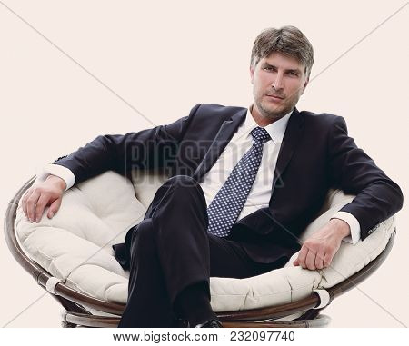 Tired business man sitting in a large comfortable chair